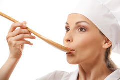 Woman cook eating with spoon, isolated on white Stock Photos