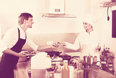 Woman cook giving to waitress ready to serve salad Stock Photos