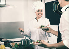 Woman cook giving to waitress ready to serve salad Royalty Free Stock Photos