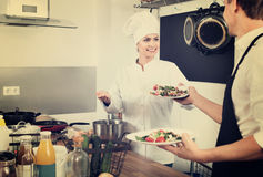 Woman cook giving to waitress ready to serve salad Stock Images
