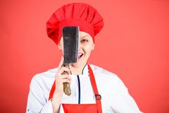 Woman in cook hat and apron. butcher cut meat. happy woman cooking healthy food by recipe. professional chef in kitchen. Cuisine. Housewife with cooking knife royalty free stock photos