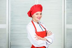 Woman in cook hat and apron. professional chef in kitchen. Cuisine. happy woman cooking healthy food by recipe royalty free stock photo