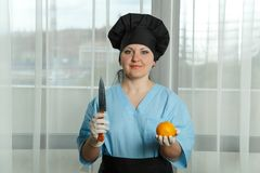 A woman cook holds an orange in her hand, and on the other hand a knife. stock images