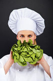 Woman cook with lettuce in her hand standing on black background Royalty Free Stock Photos