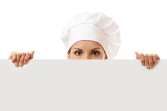 Woman cook looking over paper sign billboard. Isolated on white Royalty Free Stock Photos