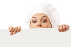 Woman cook looking over paper sign billboard. Isolated on white Stock Photos