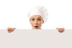 Woman cook looking over paper sign billboard. Royalty Free Stock Images