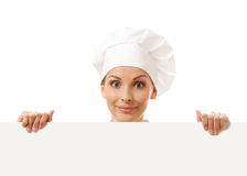 Woman cook looking over paper sign billboard. Royalty Free Stock Photo