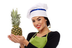 Woman cook offering pineapple Royalty Free Stock Photo