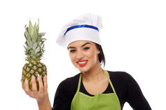 Woman cook offering pineapple Royalty Free Stock Image