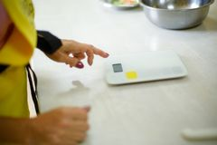 Woman cook power on kitchen scales on table royalty free stock photos