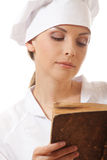 Woman cook reading recipes book Stock Images