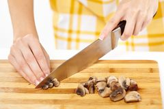 Woman cook's hands chopping mushrooms on a wooden board Stock Photo