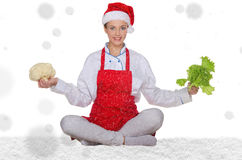 Woman cook in Santa hat, yoga, vegetables under snow Stock Images