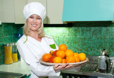 The woman the cook with a tray of fruit on kitchen Royalty Free Stock Photos