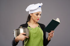 Woman with cookbook and empty pot Stock Images
