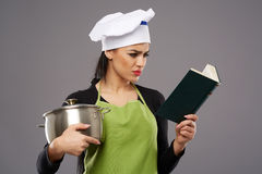 Woman with cookbook and empty pot Royalty Free Stock Photo
