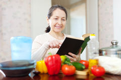 Woman  with cookbook in the kitchen Stock Photos