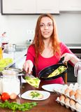 Woman  with cooked omelet  in home kitchen Royalty Free Stock Images