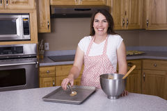 Woman cookie dough. A woman making cookies with cookie dough and putting it on a cookie sheet Royalty Free Stock Photography