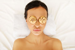 Woman with cookies on eyes enjoying spa Royalty Free Stock Images