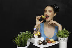 Woman with cookies. Girl eating cookies tea cookie black background stock image