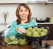 Woman cooking artichokes Stock Photos