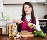 Woman cooking with avocado. Young woman cooking with avocado in home Stock Images
