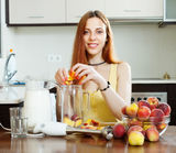 Woman cooking beverages with  blender from peaches. At domestic kitchen Royalty Free Stock Photos