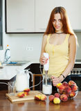Woman cooking beverages with electric blender from peaches Stock Images