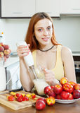 Woman cooking beverages  from nectarines and milk at  kitchen Stock Photos