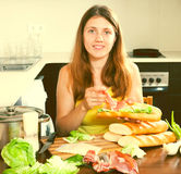 Woman cooking  bocadillo. Woman cooking spanish sandwiches (bocadillo) with hamon in home kitchen Royalty Free Stock Photography