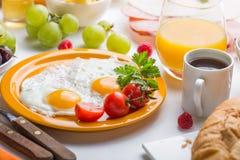 Woman cooking breakfast. Healthy breakfast ingredients, food frame. Granola, egg, dates,nuts, fruits, jam, berries, coffee, juice royalty free stock image
