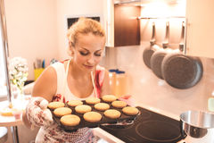 Woman cooking cakes. Smiling woman holding baking tray with muffins in kitchen. Cooking cup cakes Royalty Free Stock Photos