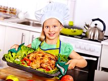 Woman cooking chicken at kitchen. Stock Photography