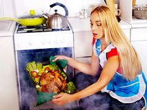 Woman cooking chicken at kitchen. Stock Photo