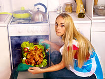 Woman cooking chicken at kitchen. Royalty Free Stock Image