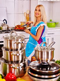 Woman cooking chicken at kitchen Royalty Free Stock Images