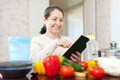 Woman cooking with cookbook in the kitchen Stock Photo