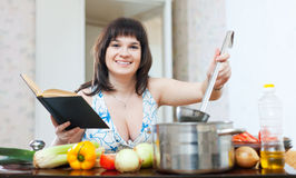 Woman cooking with cookbook Royalty Free Stock Photography