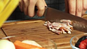 Woman cooking and cutting bacon stock footage