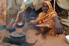 Woman Cooking in Darfur. September 22, 2004 -A woman displaced by the fighting in Darfur cooks a simple meal over an open fire outside of their family shelter in Stock Photo