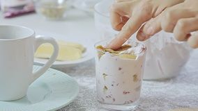 Woman cooking dessert. Woman cooking and preparing strawberry tiramisu dessert with cheese cream in transparent glass on kitchen table video footage filmed in stock video