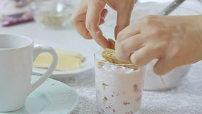 Woman cooking dessert. Woman cooking and preparing strawberry tiramisu dessert with cheese cream in transparent glass on kitchen table video footage filmed in stock video footage