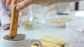 Woman cooking dessert. Woman deeping lady fingers in coffee cup and cooking strawberry tiramisu dessert with cheese cream in transparent glass on kitchen table stock footage