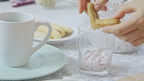 Woman cooking dessert. Woman food styling and cooking strawberry tiramisu dessert with cheese cream in transparent glass on kitchen table video footage filmed in stock video