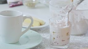 Woman cooking dessert. Woman food styling and cooking strawberry tiramisu dessert with cheese cream in transparent glass on kitchen table video footage filmed in stock video footage