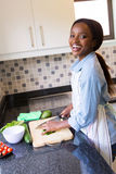 Woman cooking diner. Cheerful black woman cooking diner in kitchen Stock Photo