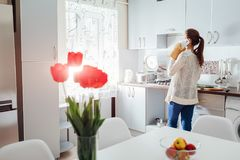 Woman cooking dinner in new kitchen and talking on the phone. Modern kitchen design. royalty free stock photos