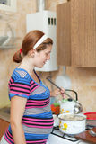 Woman cooking dumplings in the pan. On the stovetop royalty free stock photography